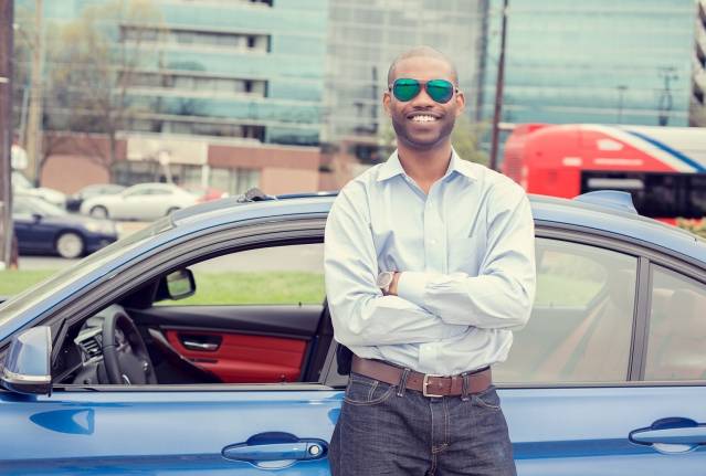 Happy man driver smiling standing by his new car